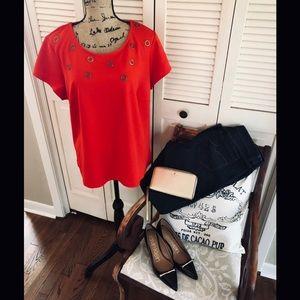 Red structured top with metal embellishments.